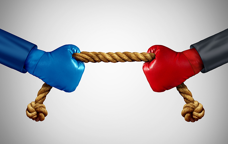 Tug of war as two opposing businessmen rivals pulling rope as a battle to win over an opponent and a test of business strength as a competition metaphor for financial strategy power between adversaries.